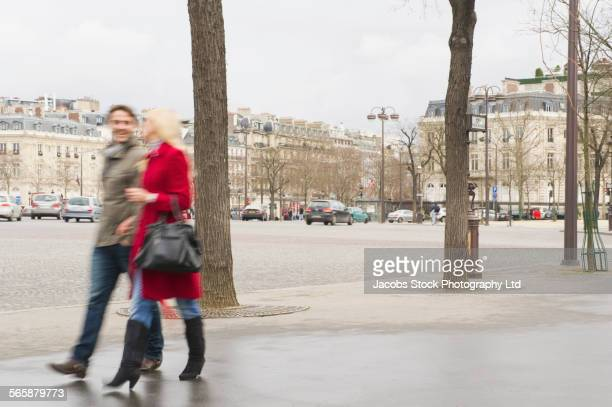 Blurred view of Caucasian couple walking on city sidewalk