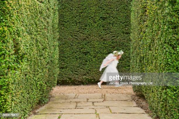Blurred view of Caucasian girl running in garden