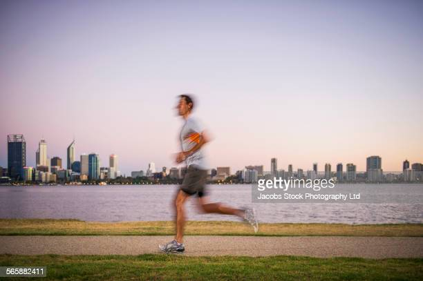 Blurred view of Caucasian man running near urban waterfront, Perth, Western Australia, Australia