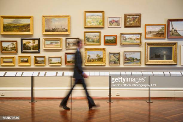 Blurred view of Caucasian security guard walking in art museum