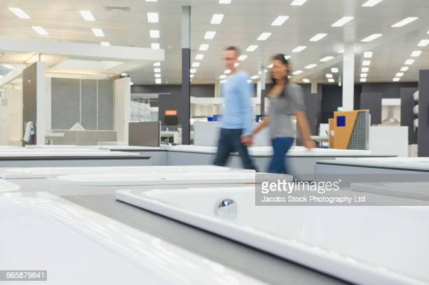 Blurred view of couple shopping for bathtub in store