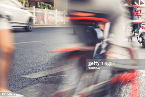 blurred  view of cyclists and traffic on street