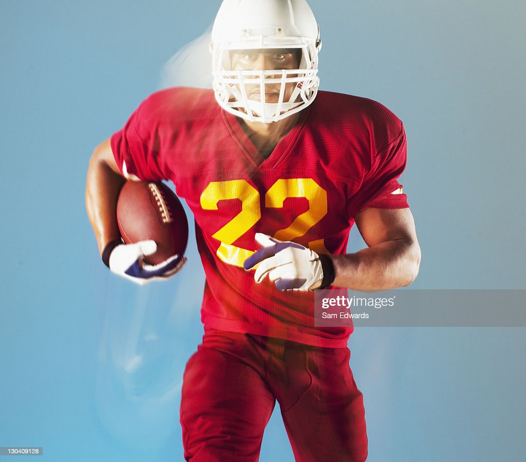 Blurred view of football player holding ball : Stock Photo