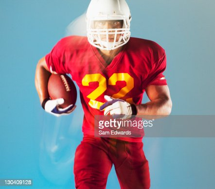 Blurred view of football player holding ball : Foto de stock