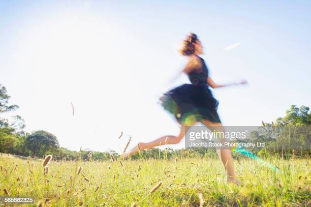 Blurred view of Hispanic woman running in field