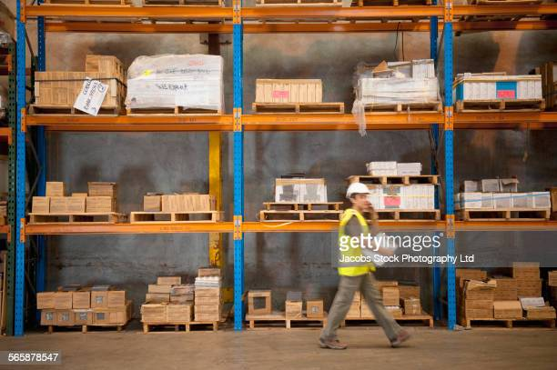 Blurred view of Hispanic worker holding clipboard in warehouse