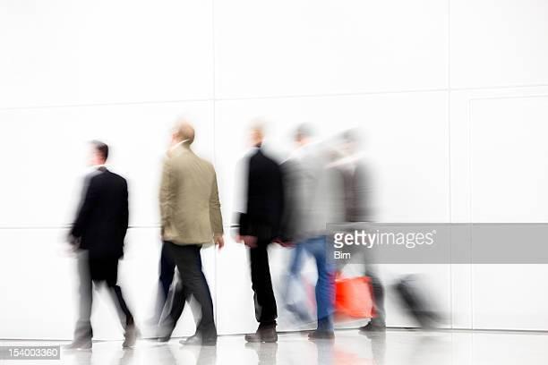 Blurred View of Men Walking Down Corridor