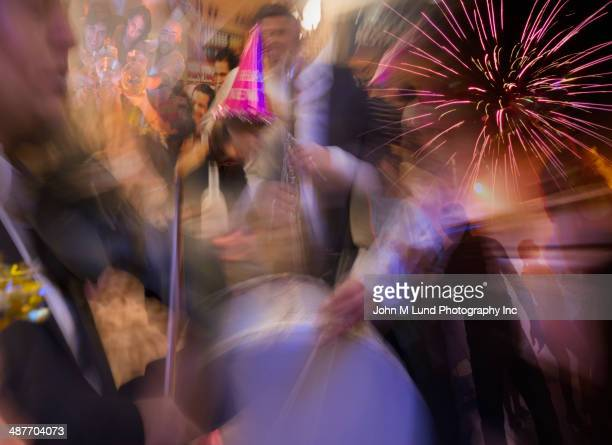 Blurred view of people dancing under fireworks at party
