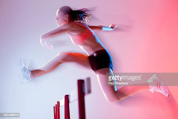 Blurred view of runner jumping hurdles
