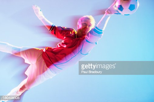 Blurred view of soccer player lunging for ball : Stock Photo
