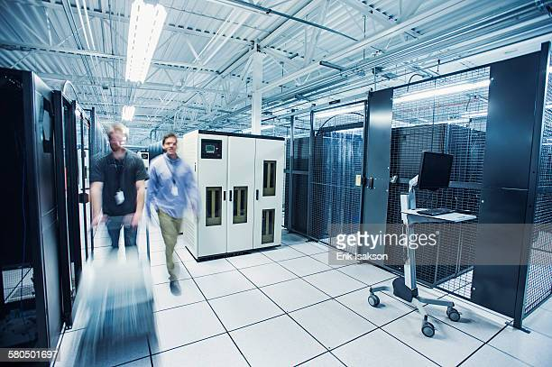 Blurred view of technicians pushing cart in server room