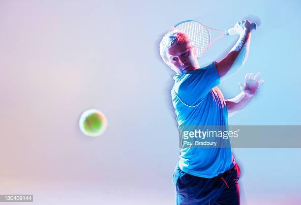 Blurred view of tennis player swinging racket