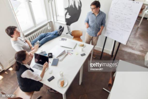 Blurred view of three creative business people having a meeting in a modern office