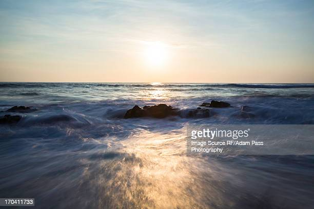 Blurred view of waves on rocky beach