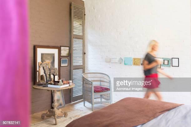 Blurred view of woman walking in bedroom