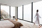 Blurred view of woman wearing bathrobe in bedroom