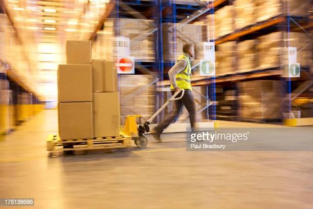 Vue floue de travailleur carting boîtes dans un entrepôt