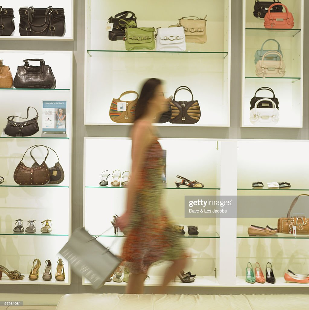 Blurred view of young woman walking in shoe store