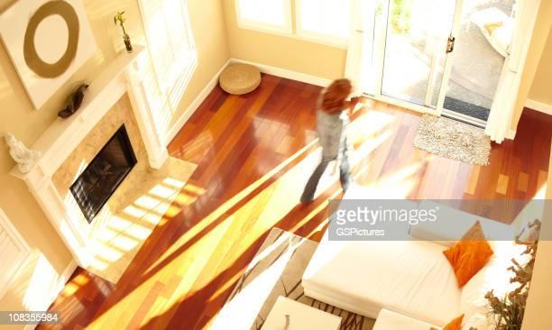 Verschwommene Frau zu Fuß durch moderne Wohnzimmer von oben