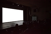 Blurry background of people watching movie in the movie theater with white screen.
