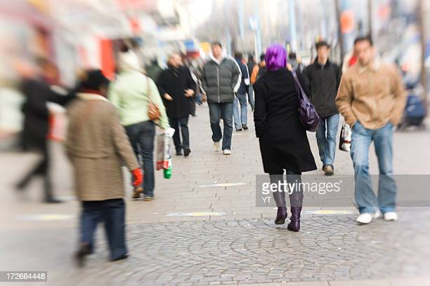 Blurry image of shoppers walking on pavement