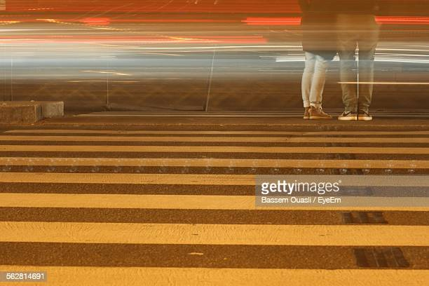 Blurry Light Trails And Couple Standing At Zebra Crossing