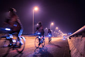 Blurry of Cyclists ride through lighted city.Background.