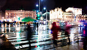 Blurry people silhouettes crossing the city street in motion blur in rainy night
