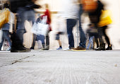 blurry people walking on the sidewalk at rush hour