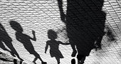 Blurry shadow of a little boy and a girl walking with adults on park pavement in black and white