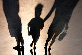 Blurry shadows of mother walking with son hand in hand and a man standing next to them