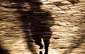 Blurry shadow silhouette of a person running on city patterned sidewalk in sepia tone