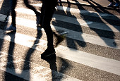 Blurry zebra crossing with  people silhouettes and  shadows in sunset