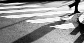 Blurry zebra crossing with silhouette and shadow of person walking in the cold and sunny early morning autumn day in black and white