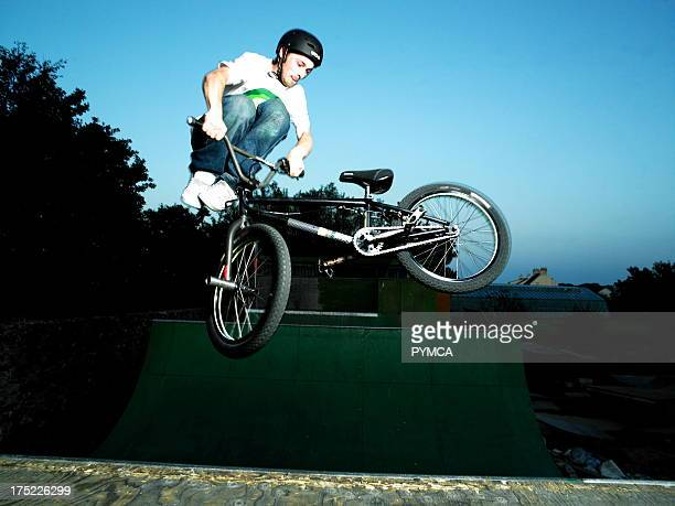 bmxer wearing a helmet doing a tailwhip on a spine ramp in guernsey