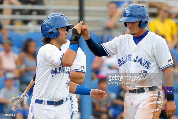 Bo Bichette of the Blue Jays congratulates Max Pentecost after they both scored a run during the Florida State League game between the Bradenton...