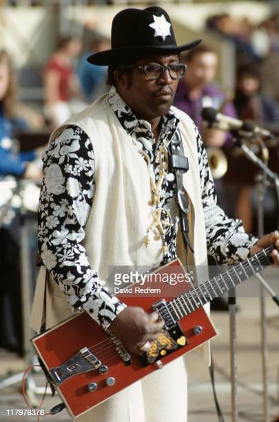 Bo Diddley rhythm and blues singersongwriter and guitarist wearing a widebrimmed hat with a decorative badge on the front and playing his trademark...