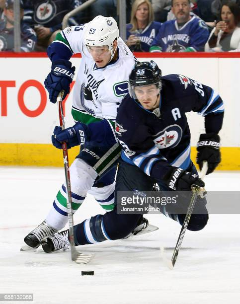 Bo Horvat of the Vancouver Canucks battles Mark Scheifele of the Winnipeg Jets for the puck during third period action at the MTS Centre on March 26...