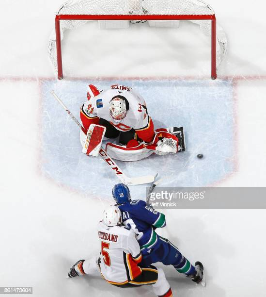 Bo Horvat of the Vancouver Canucks takes a shot against Mike Smith of the Calgary Flames during their NHL game at Rogers Arena October 14 2017 in...