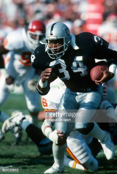 Bo Jackson of the Los Angeles Raiders carries the ball against the Kansas City Chiefs during an NFL Football game November 25 1990 at the Los Angeles...