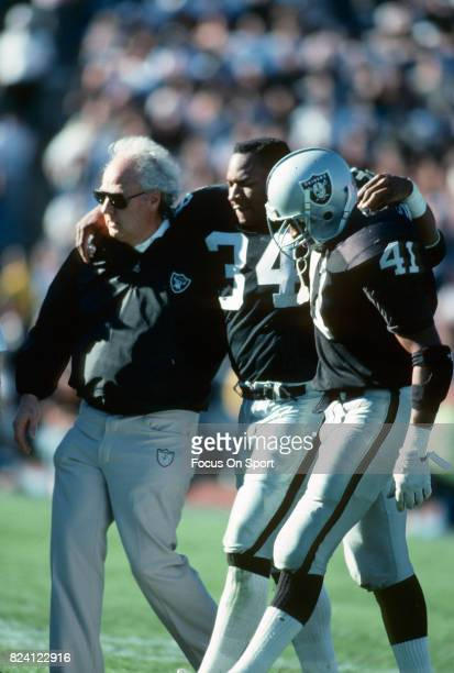 Bo Jackson of the Los Angeles Raiders get helped off the field by Napoleon McCallum after he was hurt on a play against the Cincinnati Bengals during...