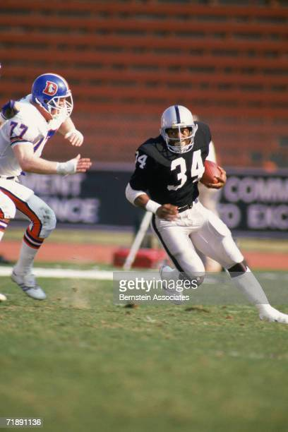 Bo Jackson of the Los Angeles Raiders rushes against the Denver Broncos at the Los Angeles Memorial Coliseum in Los Angeles California in November...