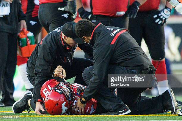Bo Levi Mitchell of the Calgary Stampeders suffers a knee injury after Aston Whiteside of the Toronto Argonauts tried to stop him during a CFL game...