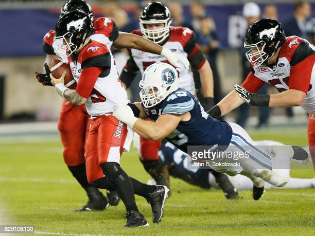 Bo Levi Mitchell of the Calgary Stampeders tries to break a tackle from Jeffrey Finley of the Toronto Argonauts during a CFL game at BMO Field on...