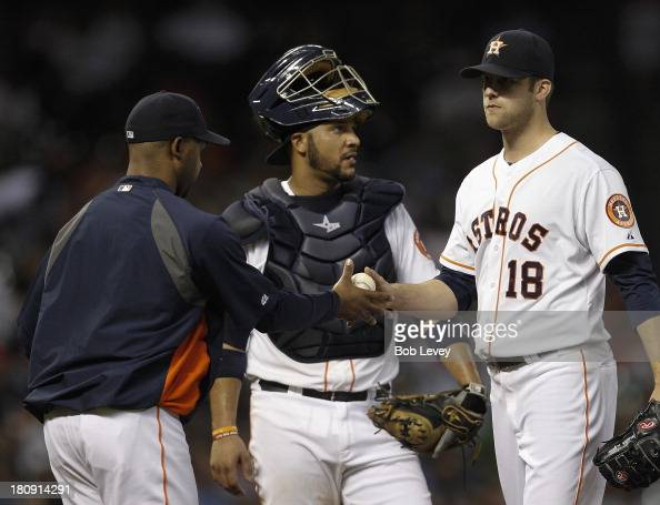 Bo Porter of the Houston Astros takes the ball from Jordan Lyles of the Houston Astros in the fourth inning as catcher Carlos Corporan of the Houston...