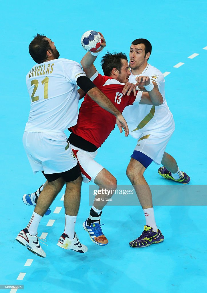 Bo Spellerberg of Denmark goes between Joan Canellas Reixach and Gedeon Guardiola Villaplana of Spain during the Men's Handball Preliminary match between Denmark and Spain on Day 4 of the London 2012 Olympic Games at The Copper Box on July 31, 2012 in London, England.