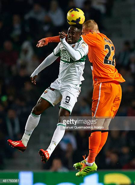 Boakye of Elche competes for the ball with Jeremy Mathieu of Valencia during the La Liga match between Elche FC and Valencia CF at Manuel Martinez...