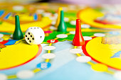 Board games for the home. Yellow, green and red plastic chips and dice on Board games for children . Selective focus
