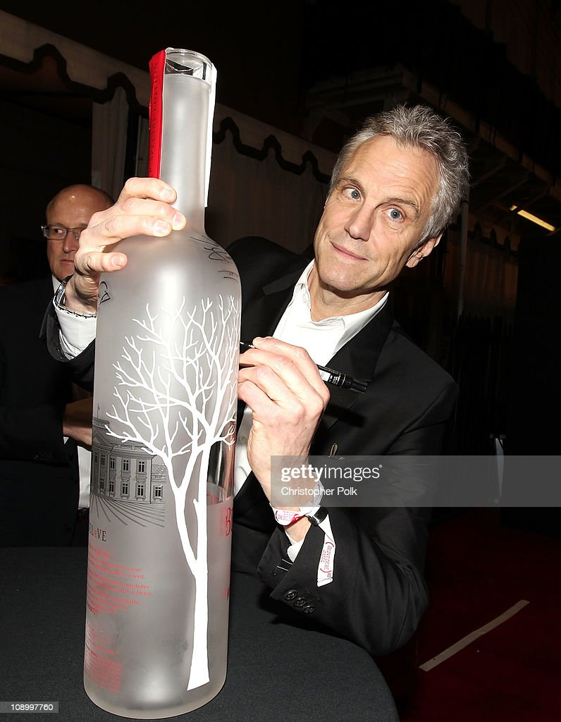 Board Member John Sykes signs the RED bottle as he arrives at the RED launches with Usher on February 10 2011 in Hollywood California