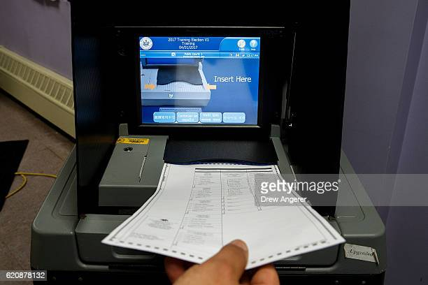 Board of Elections employee demonstrates the use of a ballot scanner at a New York City Board of Elections voting machine facility warehouse November...